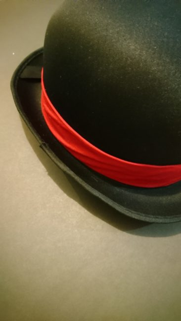 Red band of fabric slipped over derby hat